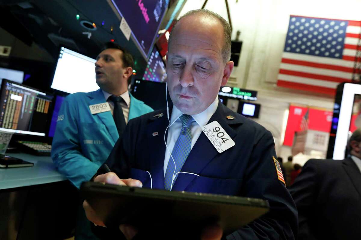 Trader Michael Urkonis works on the floor of the New York Stock Exchange, Thursday, Dec. 5, 2019. Stocks are opening slightly higher on Wall Street led by technology companies and banks. (AP Photo/Richard Drew)