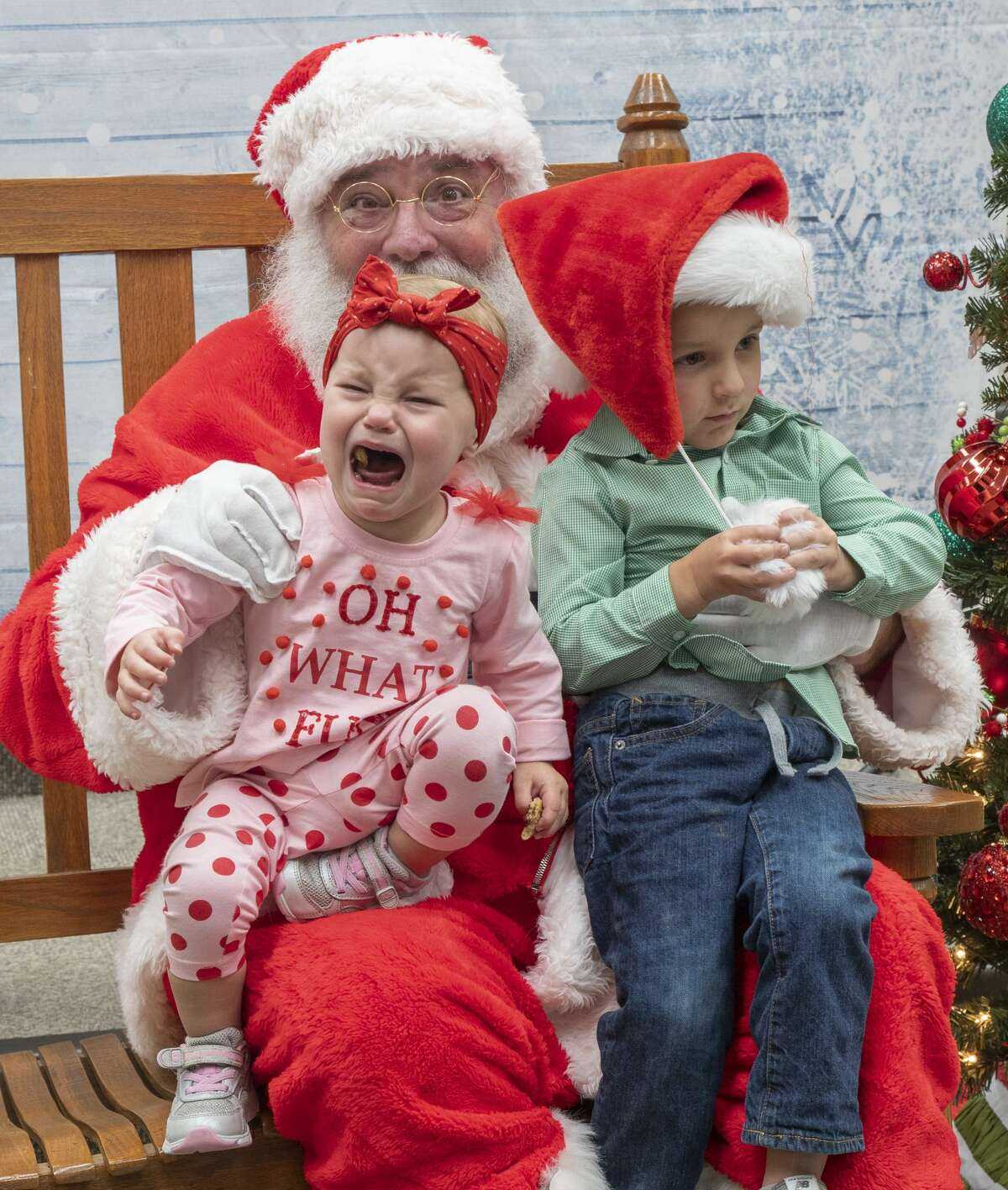 Maeve Trotter was not happy to sit with Santa and her brother Liam 12/05/19 during the Midland College holiday celebration and fall semester student art show. Tim Fischer/Reporter-Telegram