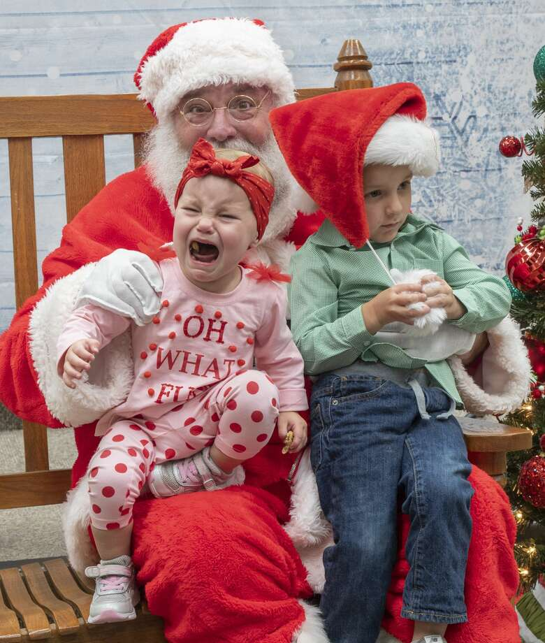 Maeve Trotter was not happy to sit with Santa and her brother Liam 12/05/19 during the Midland College holiday celebration and fall semester student art show. Tim Fischer/Reporter-Telegram Photo: Tim Fischer/Midland Reporter-Telegram