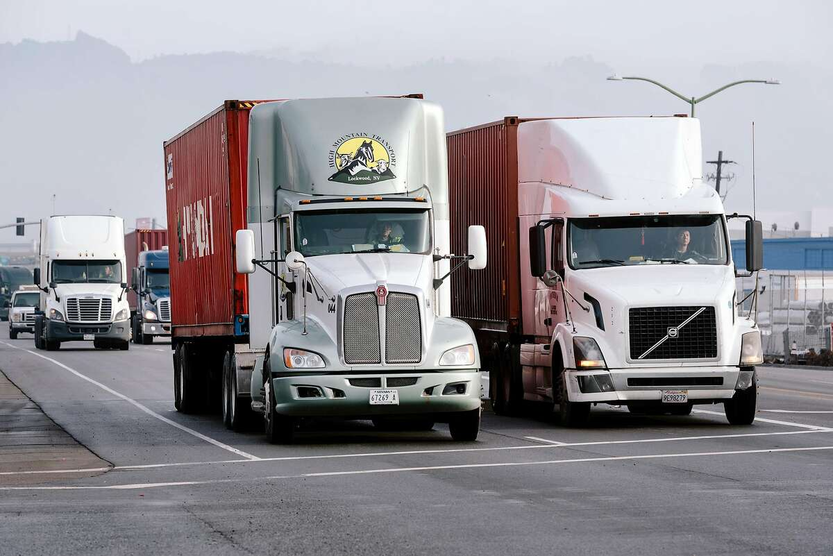 Trucks move through the Port of Oakland late last year. A state appeals court has ruled truckers in California can be classified as employees under state law.