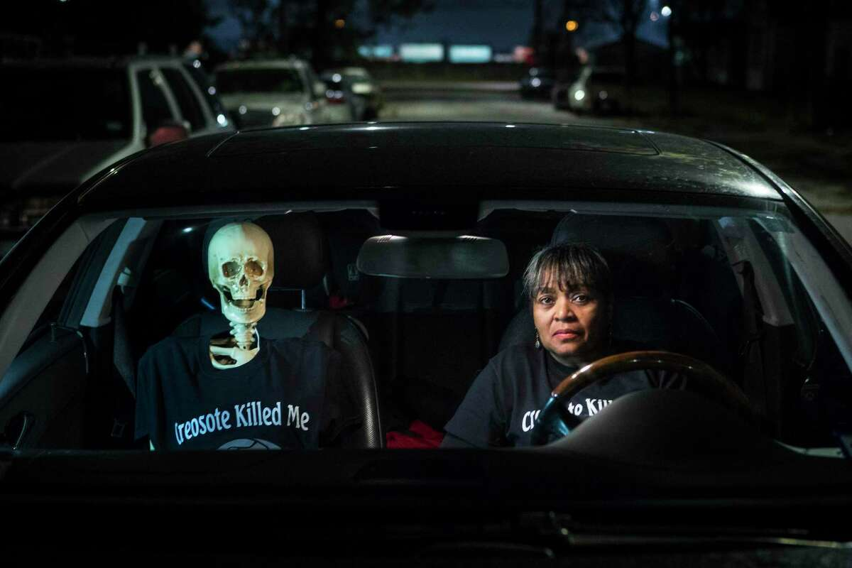"""Leisa Glenn sits in her car with a skeleton her group has dubbed """"Creosote Man"""" in their Fifth Ward neighborhood on Thursday, Dec. 5, 2019, in Houston. A cancer cluster was identified in the the historically black north Houston neighborhoods of the Fifth Ward and Kashmere Gardens, near a site of legacy contamination from rail yard operations. Creosote was used for decades to treat wooden railroad ties in the yard. Though wood treatment has ceased for many years, the creosote sunk deep into the ground, creating a plume that has moved beneath an estimated 110 homes. The cancers identified in the cluster are associated with the contaminants found in creosote."""