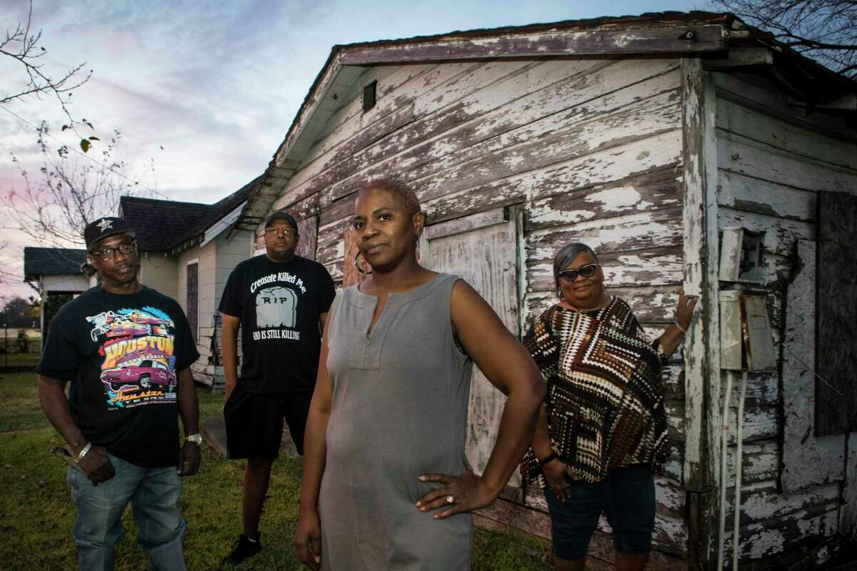 Rene Long, left, Richard Hudson, Sandra Edwards and Mary Hutchins stand in front of an abandoned home in their Fifth Ward neighborhood on Thursday, Dec. 5, 2019, in Houston. A cancer cluster was identified in the the historically black north Houston neighborhoods of the Fifth Ward and Kashmere Gardens, near a site of legacy contamination from rail yard operations. Creosote was used for decades to treat wooden railroad ties in the yard. Though wood treatment has ceased for many years, the creosote sunk deep into the ground, creating a plume that has moved beneath an estimated 110 homes. The cancers identified in the cluster are associated with the contaminants found in creosote.