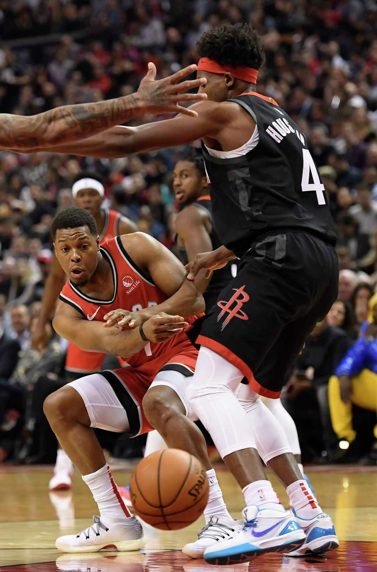Toronto Raptors guard Kyle Lowry (7) passes the ball past Houston Rockets forward Danuel House Jr. (4) during first half NBA action in Toronto on Thursday, Dec.5, 2019. (Nathan Denette/The Canadian Press via AP)