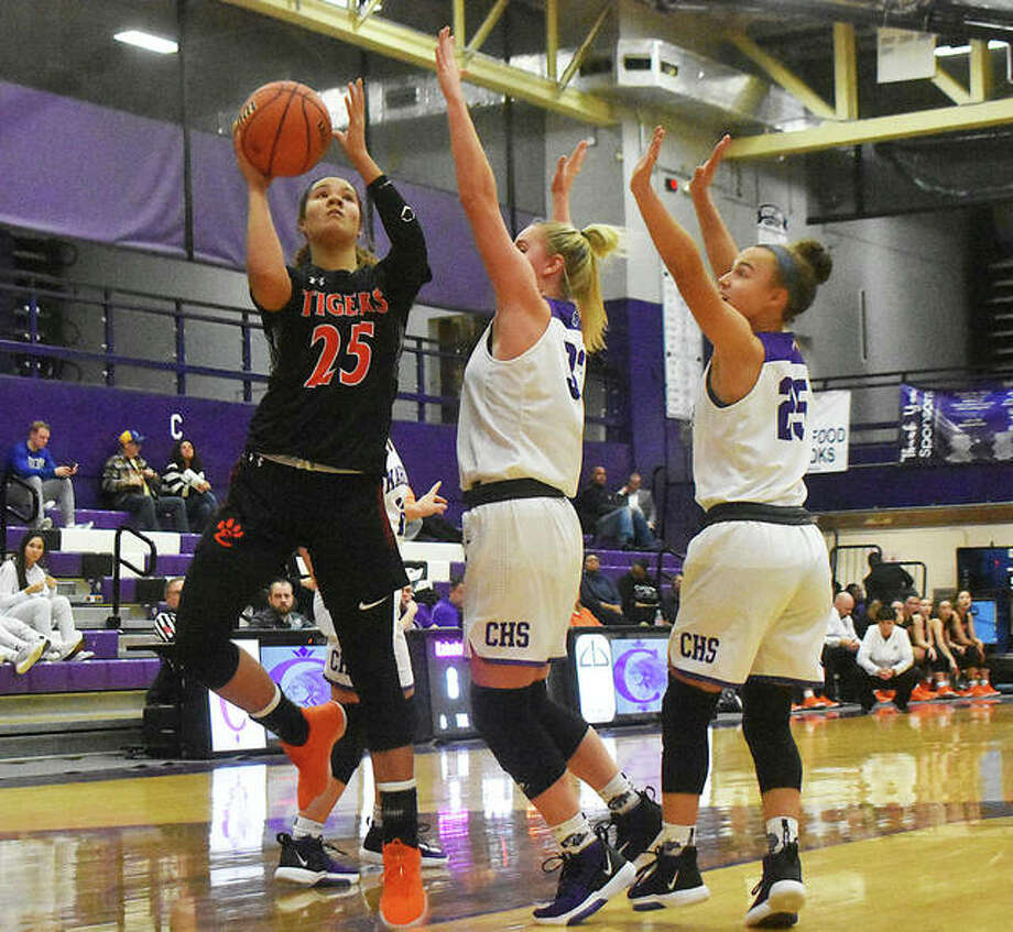 Edwardsville sophomore forward Sydney Harris, left, goes up for a shot over two Collinsville defenders in the first half. Photo: Matt Kamp|The Intelligencer