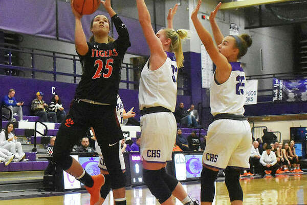 Edwardsville sophomore forward Sydney Harris, left, goes up for a shot over two Collinsville defenders in the first half.