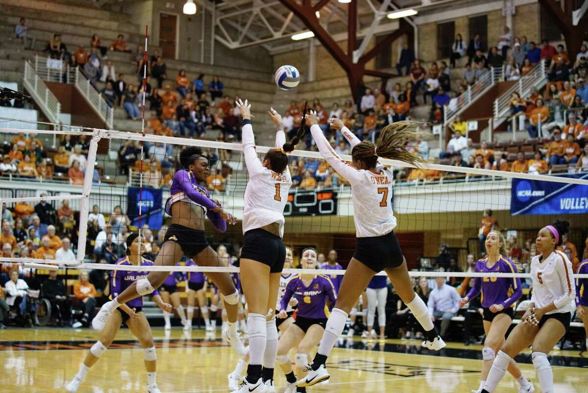 Angela Wang / Texas Athletics America East player of the Year Akuabata Okenwa, left, goes up for a kill against No. 2 Texas during the first round of the NCAA Tournament on Thursday, December 5, in Austin, Texas. UAlbany was swept by the Longhorns, 25-9, 25-16, 25-15.
