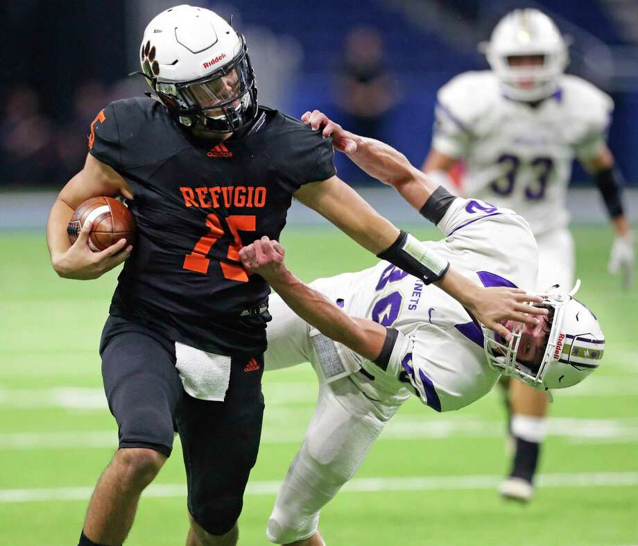 Refugio quarterback Austin Ochoa, who had a combined five touchdowns, pushes Holland defender Brady Shelton on a long run in the first half Region IV-2A Division I final on Thursday. Photo: Tom Reel / Staff Photographer / **MANDATORY CREDIT FOR PHOTOG AND  SAN ANTONIO EXPRESS-NEWS/NO SALES/MAGS OUT/TV
