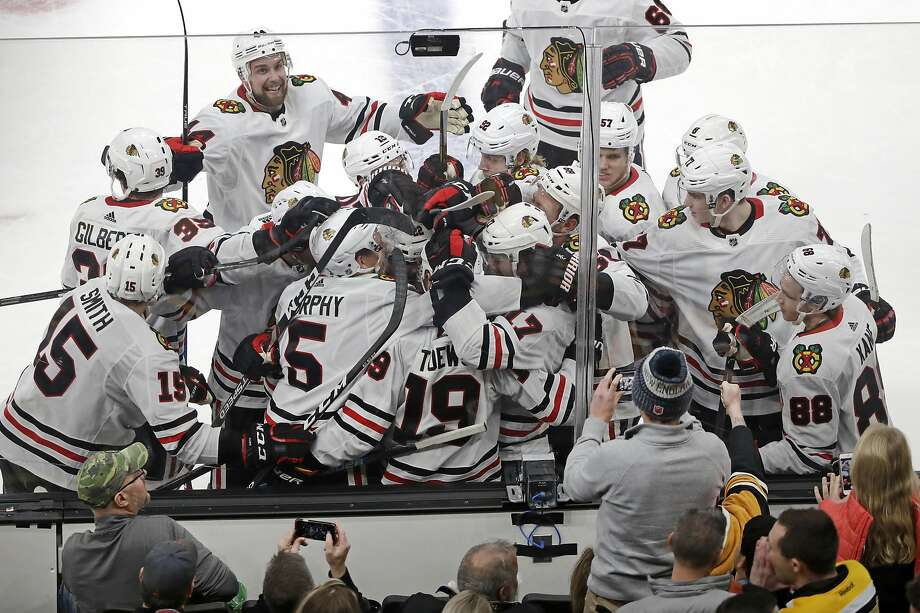 Blackhawks teammates mob Jonathan Toews (19) as they celebrate his overtime goal against the Bruins. Photo: Elise Amendola / Associated Press