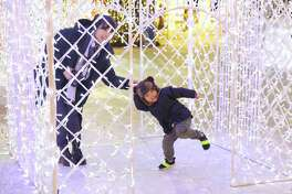 Guests explore Enchant Christmas, a traveling holiday light maze and market, which has taken over T-Mobile Park for the second year in a row, Thursday, December 5, 2019.
