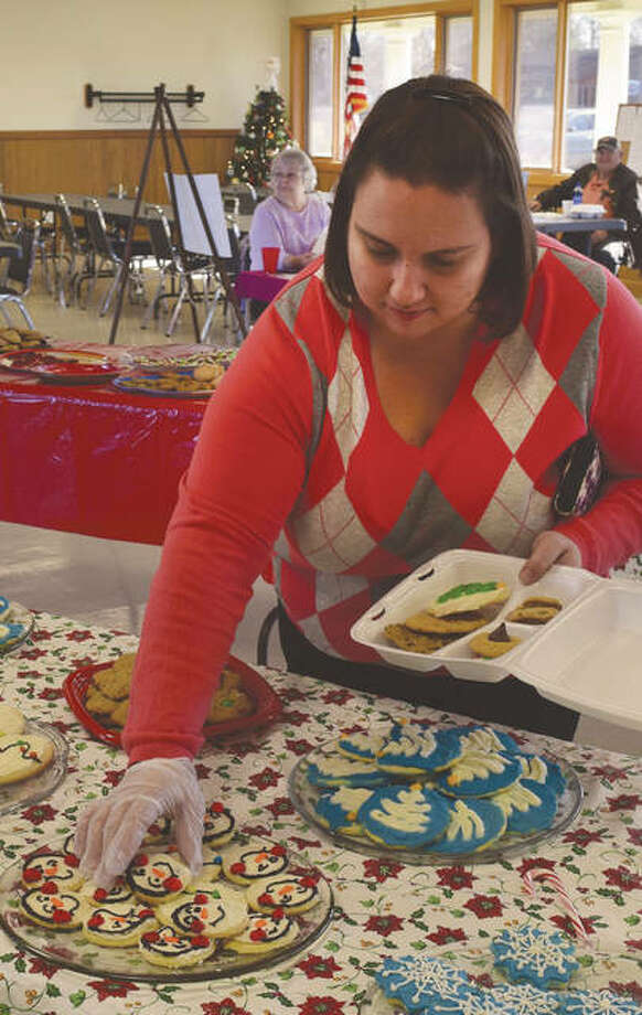 Jennifer Williams of Jacksonville selects holiday-themed homemade cookies Thursday during the Holiday Cookie and Candy Walk at the Community Park building. Jacksonville Area Senior Center organizes the event and money raised will help buy supplies to maintain the center. Photo: Marco Cartolano | Journal-Courier
