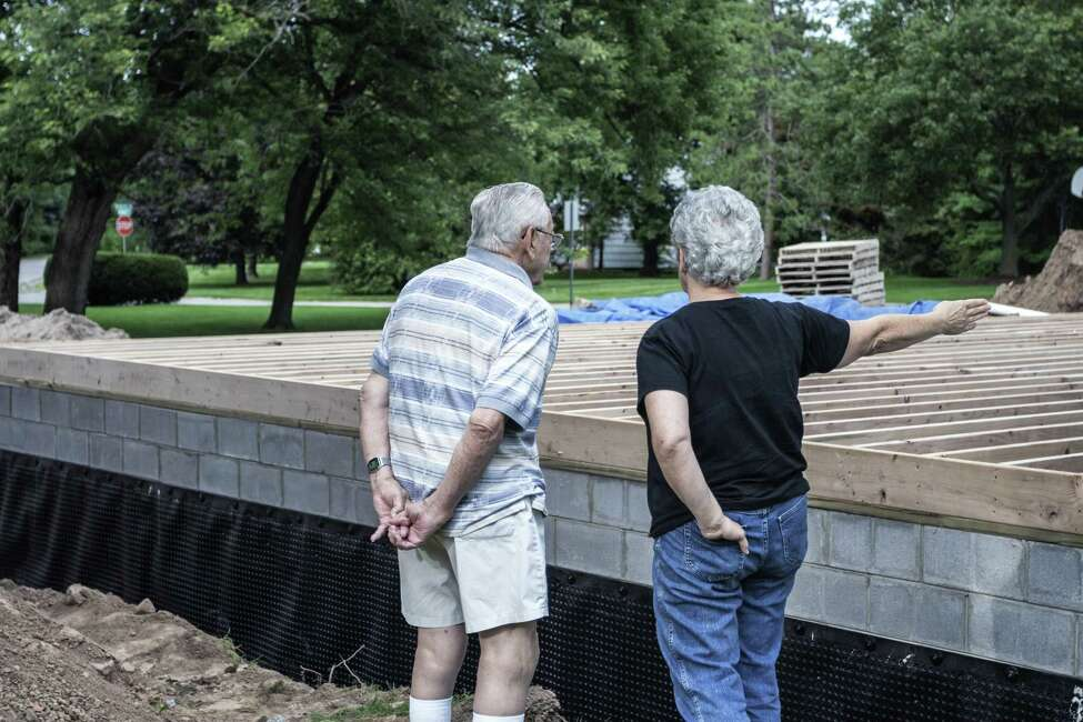 An 85-year-old father and his adult daughter discussing the home addition construction project in progress at their suburban home near Rochester, New York. This partially finished in-law apartment is being built attached to a current exterior wall of the existing family home to the right. The new apartment's concrete block basement is complete, and a heavy black plastic, waterproof, moisture barrier shroud has been permanently attached around the perimeter. This shroud will eventually be underground when the deep trench surrounding the foundation is backfilled with dirt back to ground level. Framing and completion of the first level subfloor on top of those parallel timber wood joists will begin soon.