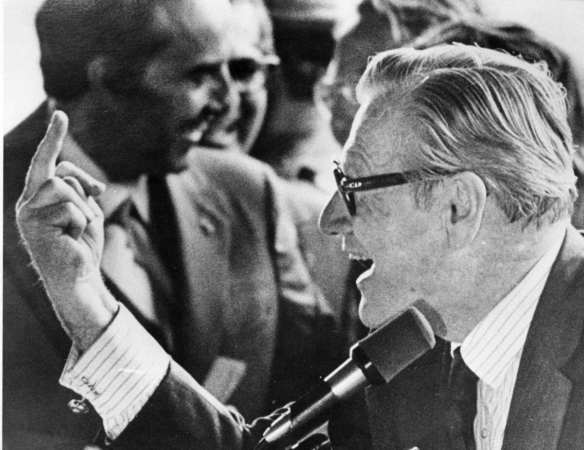 This classic photo, which was picked up and reprinted by newspapers nationwide, captures an enthusiastic Nelson Rockefeller. Rockefeller, then vice-president of the United States, was on a campaign swing through upstate New York on Sept. 16, 1976, with Sen. Bob Dole, who had been selected to be President Gerald Ford's running mate for the 1976 election. When someone in a group of heckling SUNY Binghamton students gave Rockefeller the finger, Rockefeller gave it right back, much to the delight of Dole in the background. (AP Photo/Press & Sun-Bulletin, Don Black) MANDATORY CREDIT