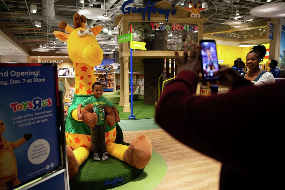 Adriana Grays takes a picture of her grandson Austin Collier, 4, during a Toys R Us store preview at The Galleria on Dec. 5, 2019.