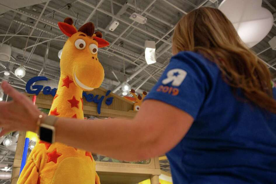 Stephanie Riley, Vice President of Retail, coaches Geoffrey the mascot before kids arrive at the new Toys R Us location in The Galleria.