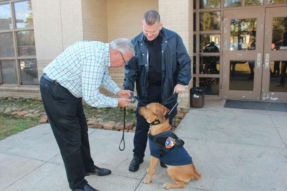 "Liberty County Sheriff Bobby Rader pinning a badge on K-9 Deputy Dog ""Red"" after swearing him in with other K-9's. Handler/Owner Deputy William Hall looks on.