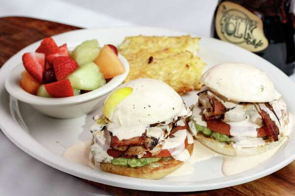 West Coast Arnold (two English muffin halves topped with Cajun turkey, bacon, tomato, guacamole, two poached eggs, and topped with Cholula ranch) at The Toasted Yolk.