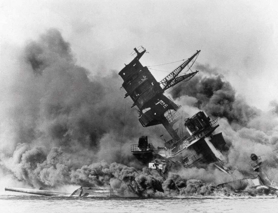 In this Dec. 7, 1941, file photo, smoke rises from the battleship USS Arizona as it sinks during the Japanese attack on Pearl Harbor, Hawaii. Photo: Associated Press / Copyright 2018 The Associated Press. All rights reserved.