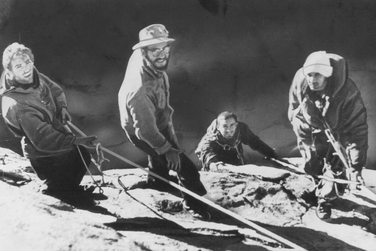 Warren Harding, far left, George Whitmore, far right, and Wayne Merry, who is just coming over the edge, complete their ascent of El Capitan in Yosemite National Park. Also pictured is George Whitmer, second from left, who is a member of the support party which greeted the climbers in 1958.