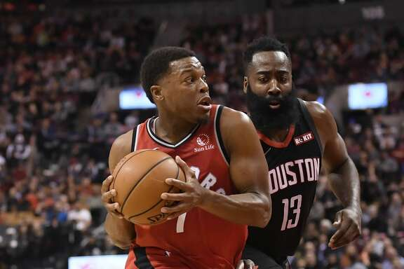 Toronto Raptors guard Kyle Lowry (7) drives past Houston Rockets guard James Harden (13) during first half NBA action in Toronto on Thursday, Dec.5, 2019. (Nathan Denette/The Canadian Press via AP)