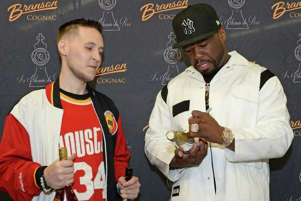 """Curtis """"50 Cent"""" Jackson's autographs bottles of his Branson Cognac and Le Chemin du Roi Champagne lines for fan Brett Ryan during a """"Meet & Greet"""" event at Spec's Wines, Spirits and Finer Foods in Sugar Land on Thursday, Dec. 5."""