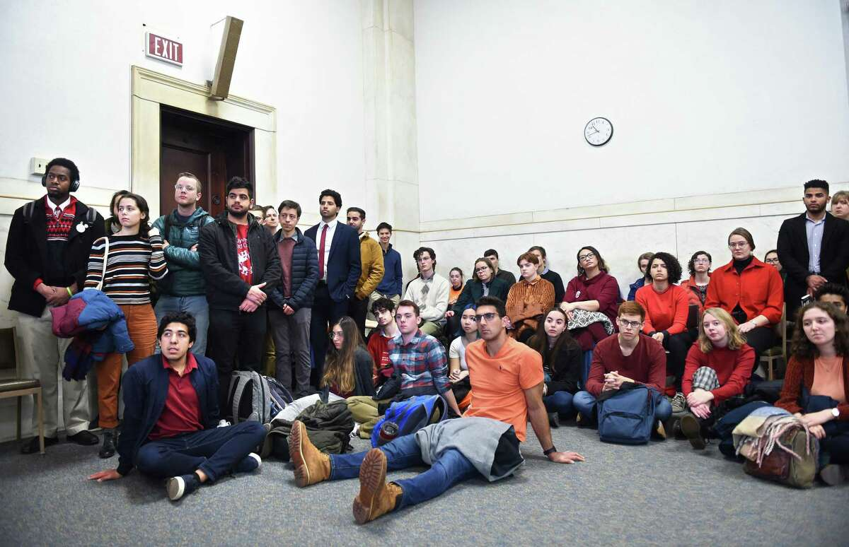 Students from Yale and Harvard University, along with others arrested at a climate change protest during halftime of the annual Yale/Harvard football game, wait in Superior Court in New Haven Friday.