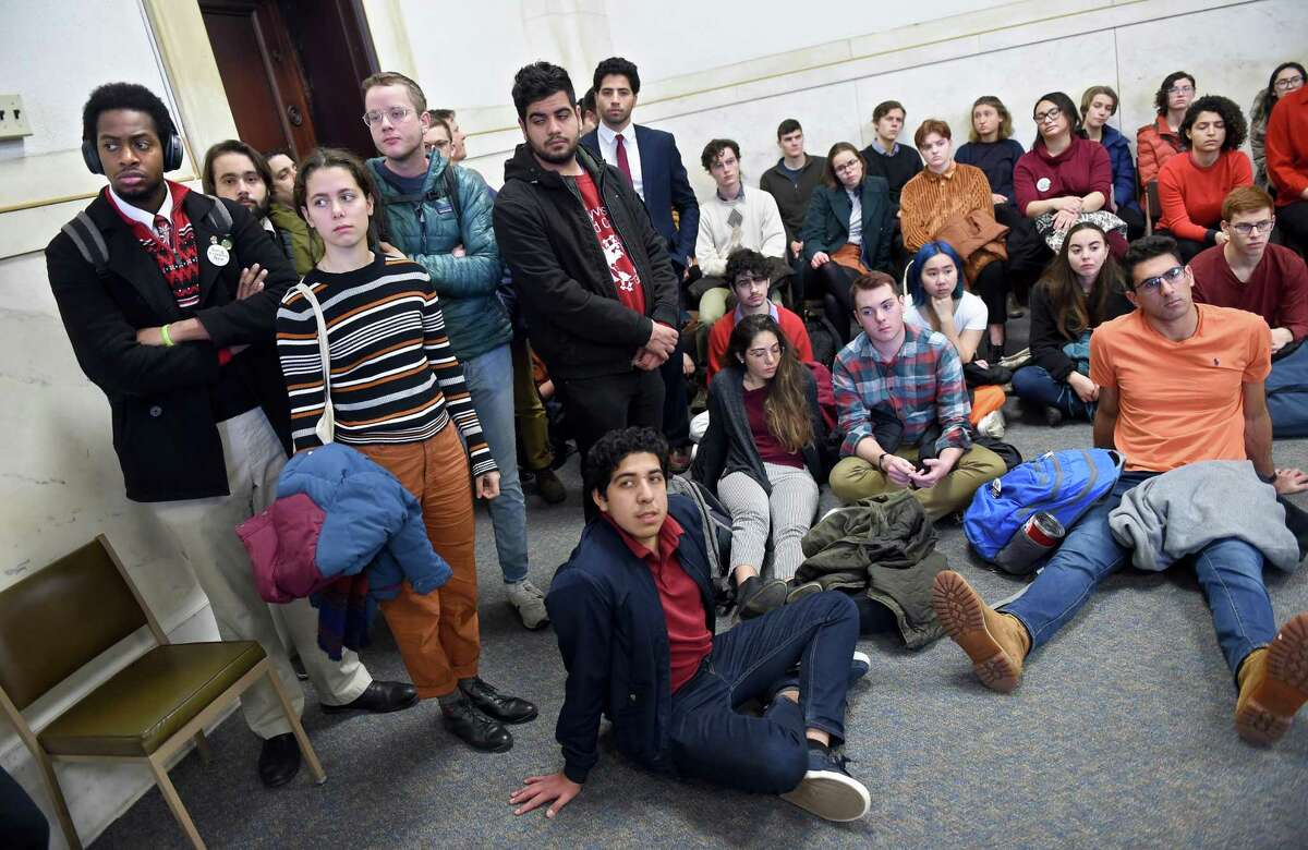 Students from Yale and Harvard University along with members of the Greater New Haven community arrested at a climate change protest during halftime of the annual Yale/Harvard football game wait in Superior Court in New Haven, Connecticut, for their arraignments on December 6, 2019.