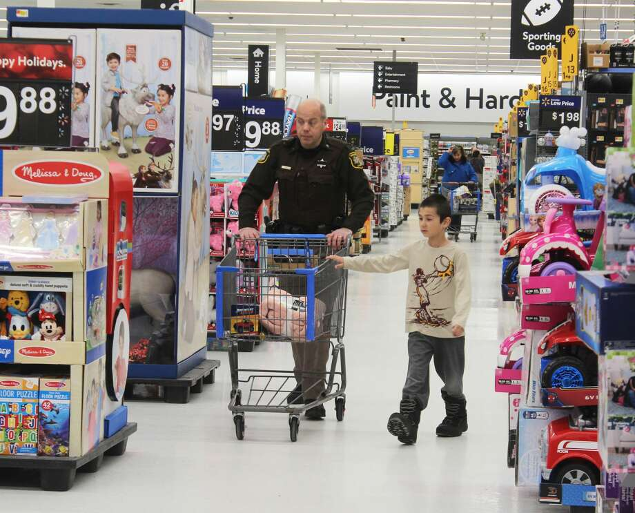 Members of local law enforcement helped 15 Mecosta County students shop for Christmas presents for family and friends during the annual Shop with a Cop event Thursday. During this event, kids and the first responders they were paired with spent the day enjoying a variety of activities, including an art lesson at Heartfull Art Studio, dinner at The Rock Cafe and a parade of lights through town before the main shopping trip at Walmart. Photo: (Pioneer Photo/Taylor Fussman)