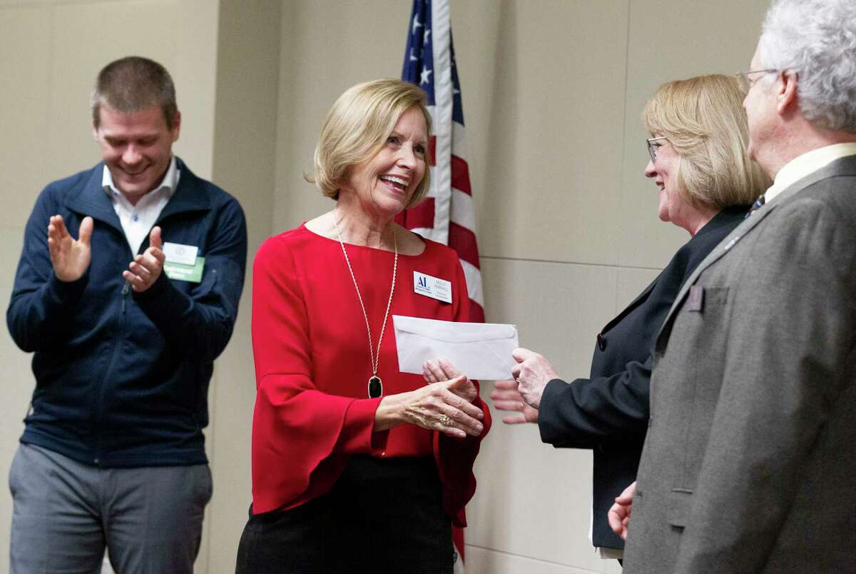 Molly Parkhill with the Montgomery County Assistance League accepts a check for $7,200 from Amanda Trapp, vice president of the Montgomery County Community Foundation, on behalf of the nonprofit during the Montgomery County Community Foundation grant reception at Memorial Hermann The Woodlands Hospital, Thursday, Dec. 5, 2019, in The Woodlands. The foundation granted $184,100 to 43 local nonprofits. The funds for MCAL will be used for new school clothes and literacy under Operation School Bell to help economically disadvantage youth in Montgomery County schools.