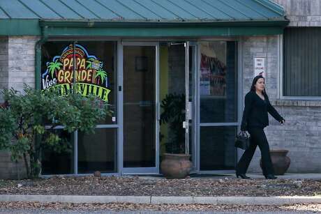 A woman exits the front doors of Garcia Foods at 1802 Jackson Keller on Tuesday. Assets of the company were sold at a bankruptcy auction Friday.