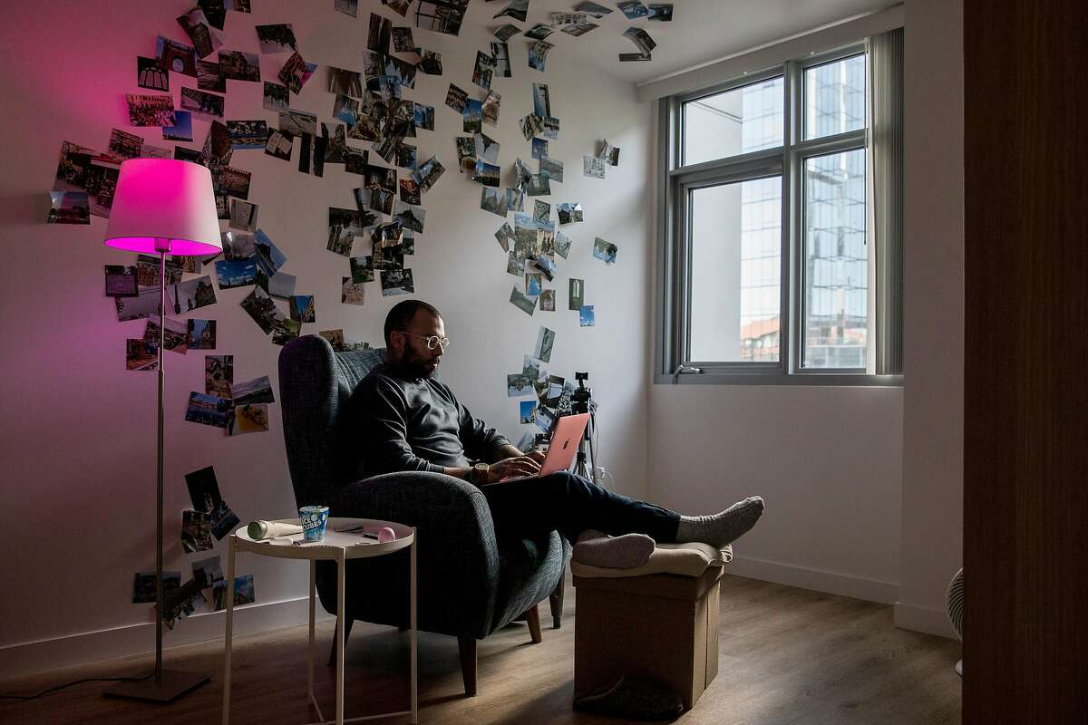 Adrian Caratowsa uses his computer while relaxing in the living room of his apartment inside the Natalie Gubb Commons in the South of Market district of San Francisco, Calif. Thursday, Nov. 21, 2019.