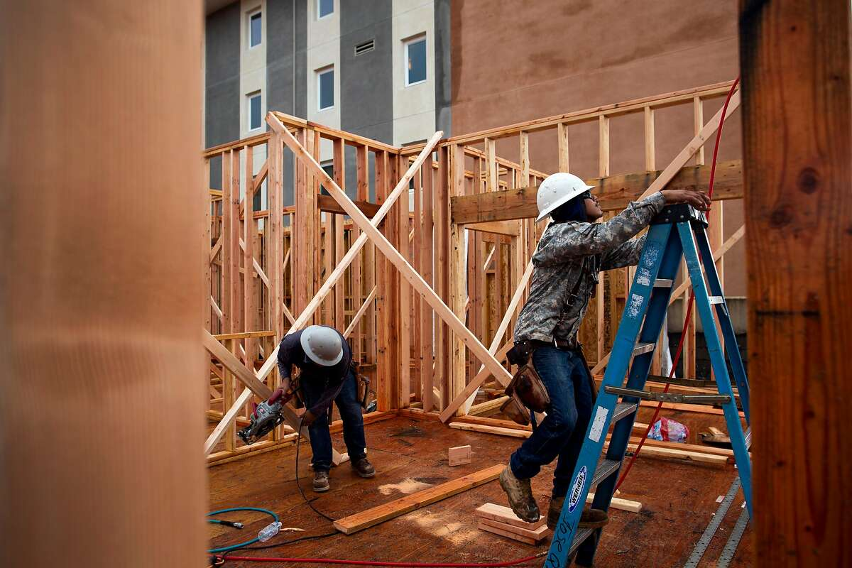 """Eleazar Altamirano (left) and Alejandro Basurto (right) building """"Art House """" a development by Hugh Futrell, on Riley Street, at 7th in Santa Rosa, California, December 5th, 2019. Piece on Santa Rosa's efforts to stimulate more downtown housing -- mostly just plans so far, not action, despite strong push by city. Will also touch on how rebuilding efforts continue to move briskly in the wake of 2017 fire -- but focus is downtown, and efforts to invigorate it. The one site downtown with housing construction at present is the Art House development on Riley Street, at 7th."""