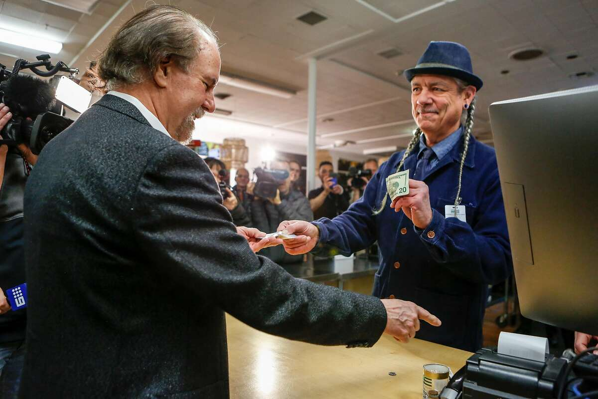 CEO of Harborside Health Center, Steve DeAngelo (right), makes the first sale at 6am to Henry Wyckowski on the first day of recreational marijuana sales in California on Monday, January 1, 2018 in Oakland, California.