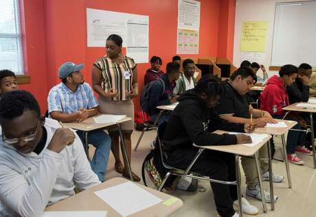 Miles Ahead Scholars English and Instructional Specialist Jaelynn Robinson helps Worthing High School student Christopher Olivio doing a worksheet during a class to learn about identity on Tuesday, Oct. 29, 2019, in Houston. The program, which was piloted by state Sen. Borris Miles at the urging of Lt. Gov. Dan Patrick, identifies high-potential freshmen and sophomore male students at three HISD high school and aims to get them enrolled in the nation's most prestigious universities.