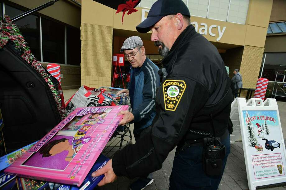 Norwalk resident William Alastor contributes to officer Bruce Lovallo and the Norwalk Police Department's Stuff A Cruiser campaign to help children in need Friday, December 6, 2019, at Walmart on Main Ave. in Norwalk, Conn. Officers accepted donations of new, unwrapped toys for children ages infant-15 years old which benefit local families in need through Department's Community Policing Division, The Domestic Violence Crisis Center, The Human Services Council, The Open Door Shelter and The Norwalk Housing Authority. Photo: Erik Trautmann / Hearst Connecticut Media / Norwalk Hour