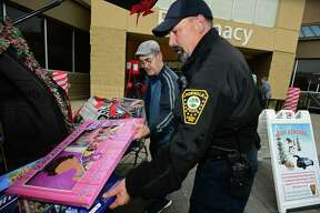 Norwalk resident William Alastor contributes to officer Bruce Lovallo and the Norwalk Police Department's Stuff A Cruiser campaign to help children in need Friday, December 6, 2019, at Walmart on Main Ave. in Norwalk, Conn. Officers accepted donations of new, unwrapped toys for children ages infant-15 years old which benefit local families in need through Department's Community Policing Division, The Domestic Violence Crisis Center, The Human Services Council, The Open Door Shelter and The Norwalk Housing Authority.
