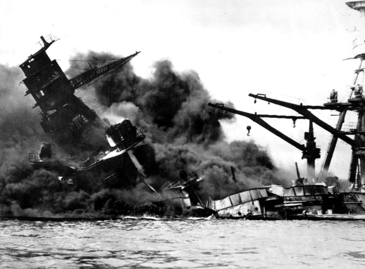 The battleship USS Arizona belches smoke as it topples into the sea during the Japanese surprise attack on Pearl Harbor.