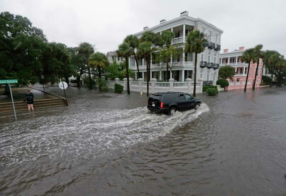 FILE - In this Oct. 3, 2015, file photo, a driver takes his truck through a flooded street in Charleston, S.C. Historic coastal cities in the Southeast U.S. have survived disease outbreaks, wars and hurricanes over the past three centuries. Now they are trying to figure how to survive rising seas from climate change. (AP Photo/Chuck Burton, File)