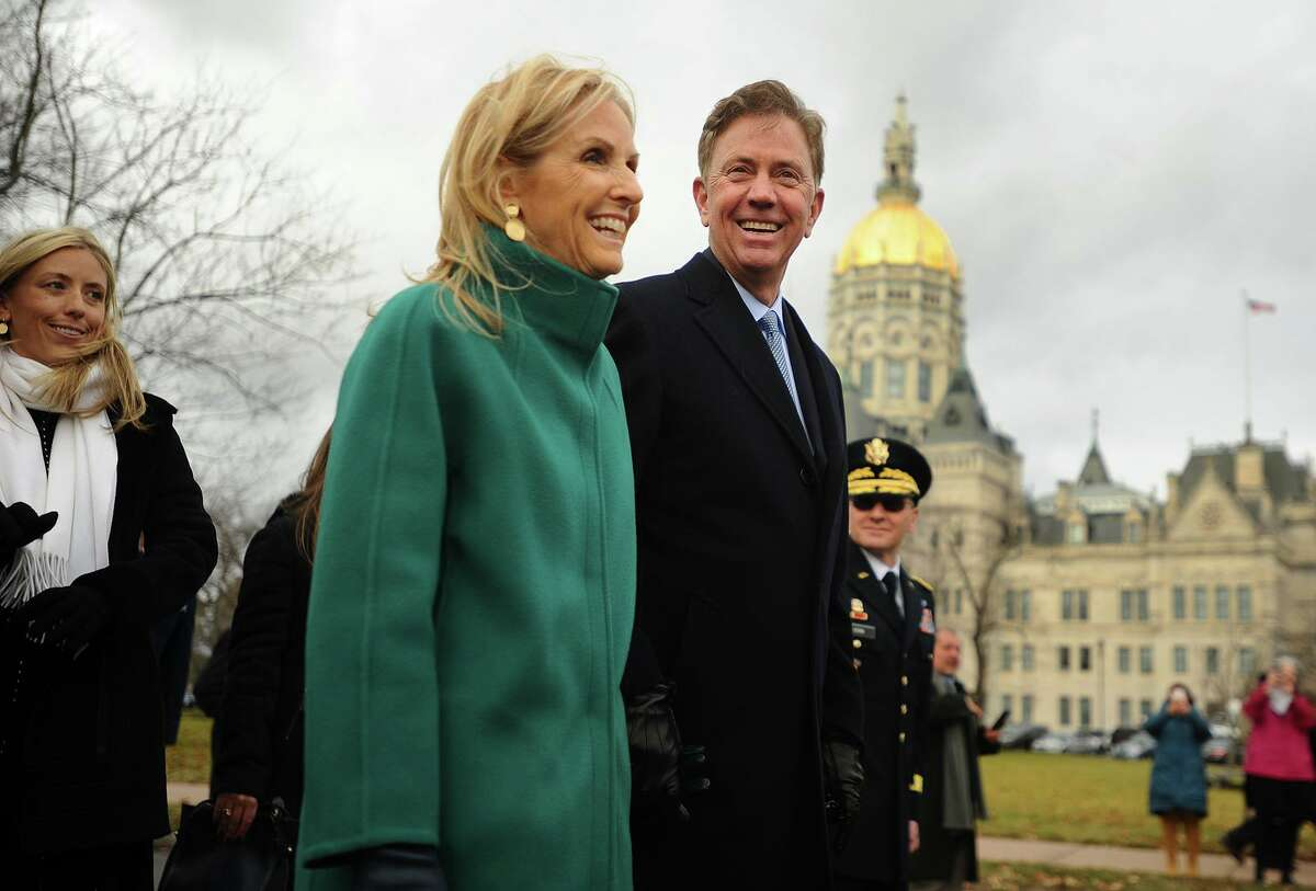 Flanked by daughter Lindsay, left, and wife Annie, newly sworn in Governor Ned Lamont marches in a parade past the Capitol in Hartford in January 2019.