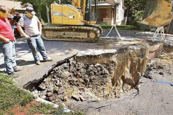 In this 2016 file photo, workers are on the scene of a large sinkhole on West 9th Street in Alton just south of State Street.