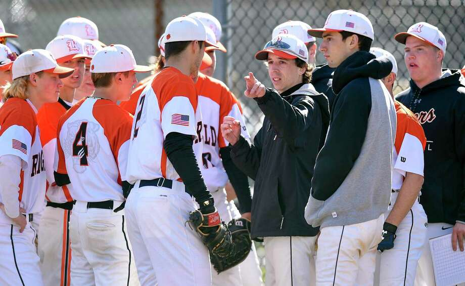 Ridgefield JV Coach Mike Scarlett, center, talks with players prior to taking the field against Stamford in an FCIAC baseball game on Wednesday, April 10, 2019 in Stamford, Connecticut. Scarlett, assumed the coaching duties of the varsity baseball team after three coaches were put on administrative leave following a baseball field fire. Photo: Matthew Brown / Hearst Connecticut Media / Stamford Advocate