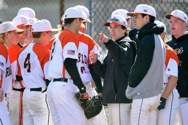 Ridgefield JV Coach Mike Scarlett, center, talks with players prior to taking the field against Stamford in an FCIAC baseball game on Wednesday, April 10, 2019 in Stamford, Connecticut. Scarlett, assumed the coaching duties of the varsity baseball team after three coaches were put on administrative leave following a baseball field fire.