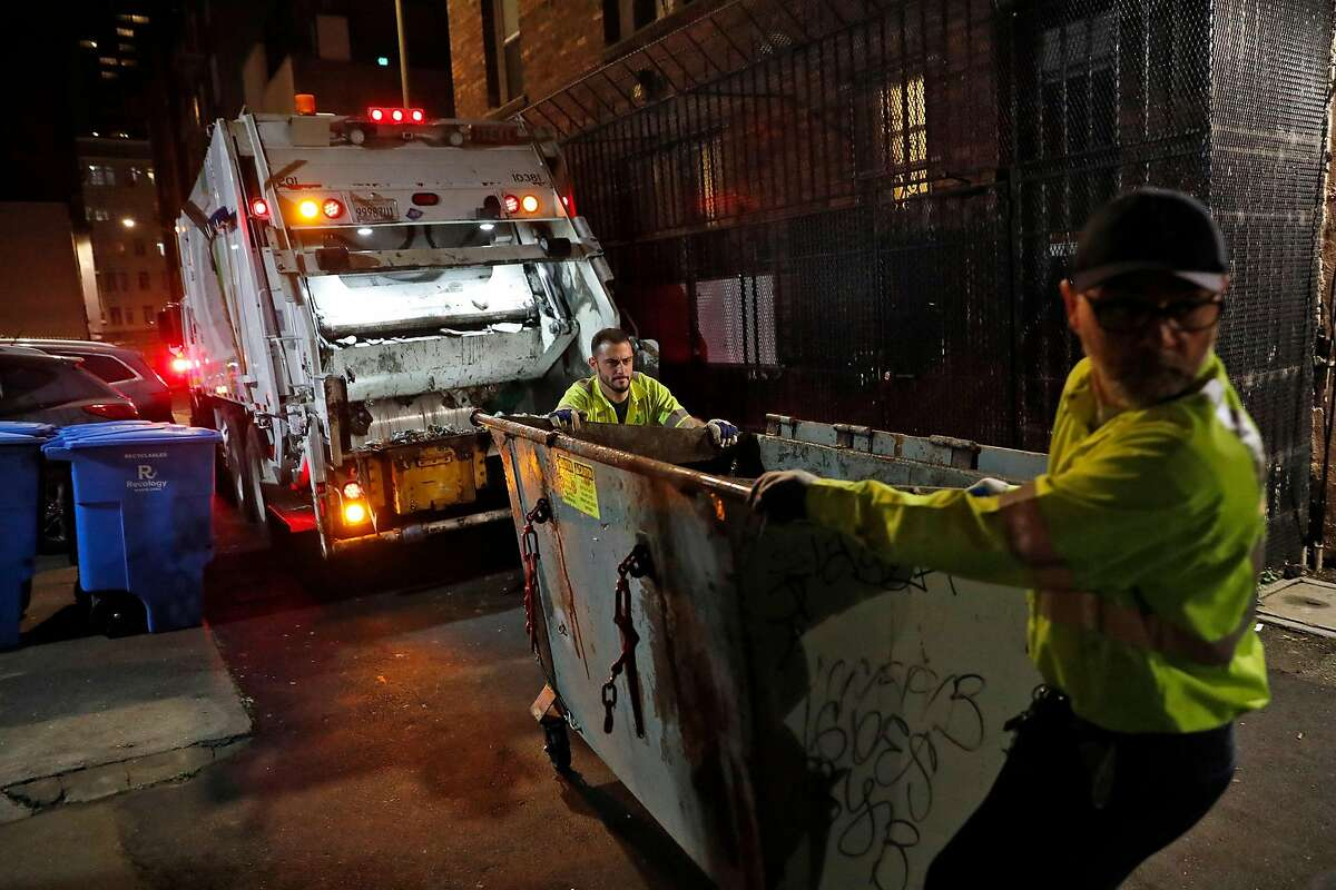 Recology's Bobby Carin (left) and Ron Reali return a dumpster after emptying it in Antonio Alley in the Tenderloin District in San Francisco, Calif., on Tuesday, December 3, 2019.