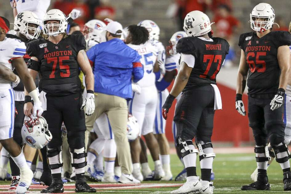 Houston Cougars offensive lineman Jack Freeman (75), offensive lineman Keenan Murphy (77) and offensive lineman Gio Pancotti (65) watch as the SMU Mustangs celebrate after beating the Houston Cougars in an NCAA football game at TDECU Stadium on Thursday, Oct. 24, 2019, in Houston.