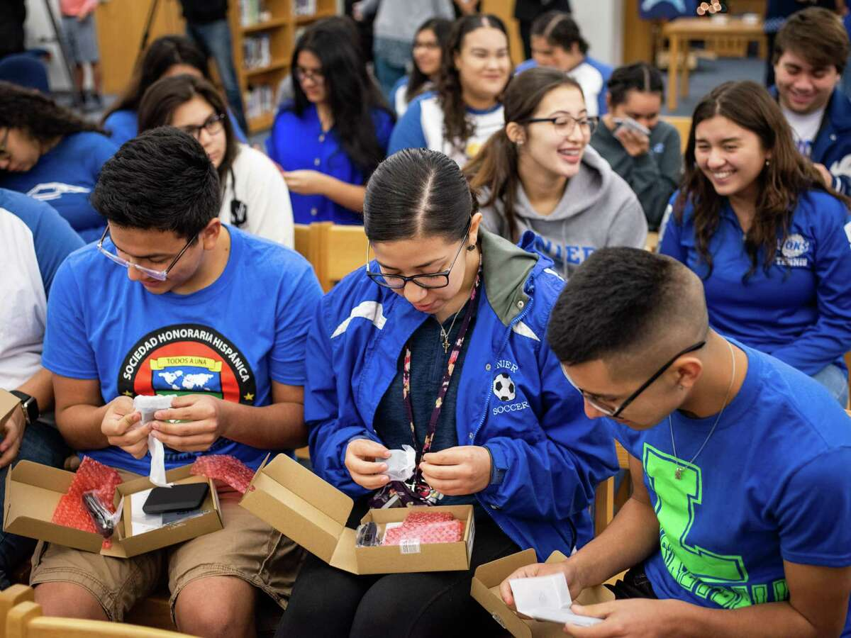 From front left, Ray Rocha, Emily Rocha, and Steven Sanchez unbox their new, free hotspot devices at Sidney Lanier High School on Friday. SAISD partnered with 1Million Project Foundation to supply 5,200 high school students throughout the district with free wireless connectivity via smart phones or hotspot devices for their homes.