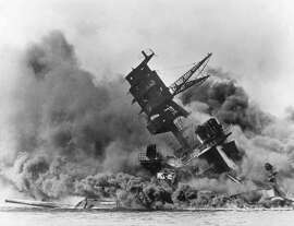 FILE - In this Dec. 7, 1941 file photo, smoke rises from the battleship USS Arizona as it sinks during the Japanese attack on Pearl Harbor, Hawaii. Divers will place the ashes of Lauren Bruner, a survivor from the USS Arizona in Pearl Harbor, in the wreckage of his ship during a ceremony this weekend.  Bruner died earlier in 2019 at the age of 98. (AP Photo, File)