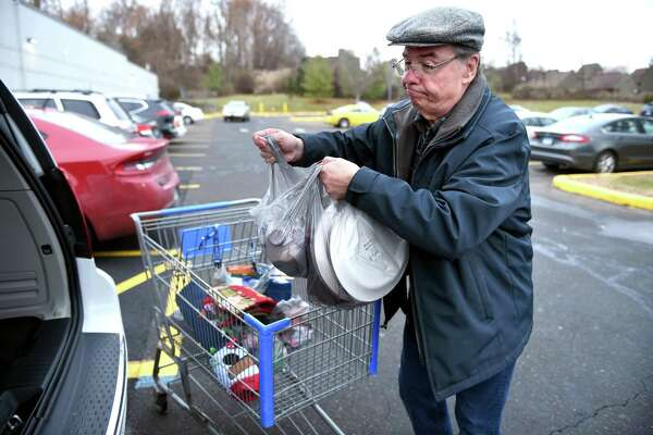 David Rowland of Guiford loads single-use plastic bags into his vehicle at Walmart in Branford Dec. 6, 2019. Rowland usually has reusable bags with him but made an unplanned stop at the store.