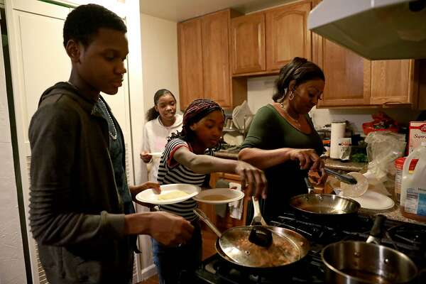 Sonja Johnson, right, cooks chicken tacos for her grandchildren, Yasir Robinson, 13, left, and Jay'Miiah Long, 12, center, along with close family friend, Tany'Jah Aldridge, 13, back, whom Johnson says feels like a daughter, during dinner time at their home in Oakland, Calif., on Tuesday, December 3, 2019. The Season of Sharing Fund was able to help Johnson with a deposit for a three-bedroom home in Oakland, so there's enough space for her three grandchildren.