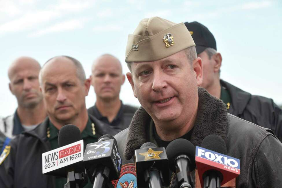 Navy Capt. Tim Kinsella briefs members of the media following a shooting at the Naval Air Station in Pensacola, Fla., Friday, Dec. 6, 2019. The US Navy is confirming that a shooter is dead and several injured after gunfire at the Naval Air Station in Pensacola. (Tony Giberson/Pensacola News Journal via AP)