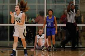 Lake Creek forward Sage Marcos (22) reacts after shooting guard Makenzie Logeman (1) hits a buzzer beating shot to end the first quarter of a District 20-5A high school girls basketball game at Lake Creek High School, Friday, Dec. 6, 2019, in Montgomery.