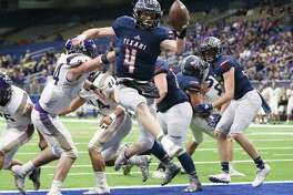 Wimberley quarterback Cooper McCollum (04) leaps into the end zone for a touchdown in the fourth quarter against Navarro's Gabriel Means (34) during their state quarterfinals football game at the Alamodome on Friday, Dec. 6, 2019. The Texans defeated the Panthers to advance the semifinals, 42-12.